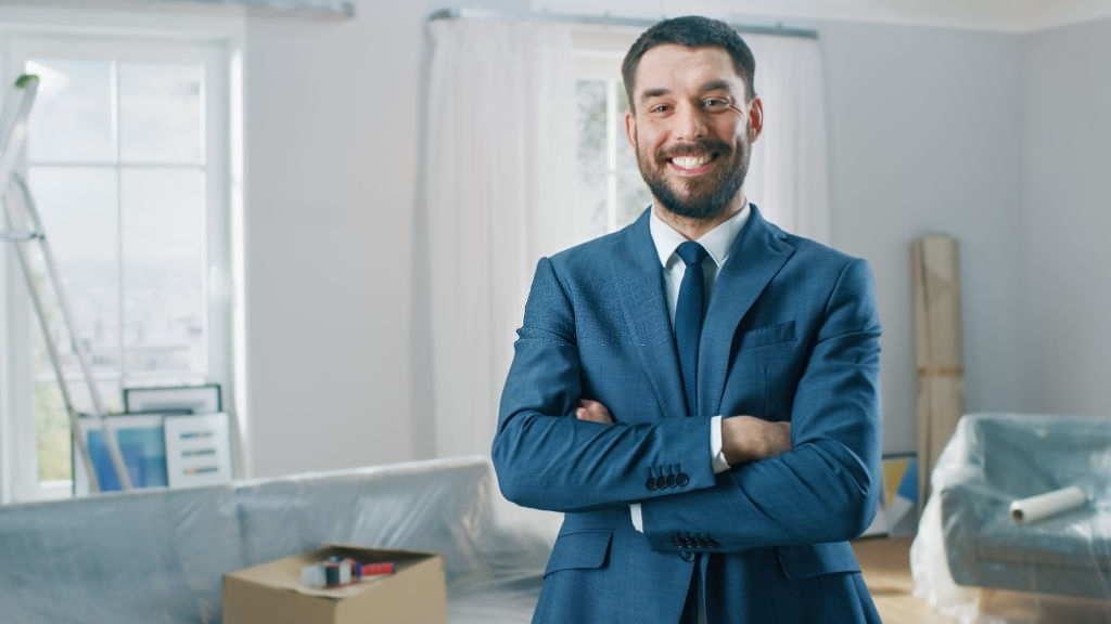 Successful Real Estate Agent in a Suit Smiles and Offers Keys From a New Apartment. Standing in the Middle of Room that Being Renovated. Spacious New House for Sale by Professional Real Estate Broker.